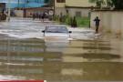 Homem passa com carro quase coberto pela água. Enchente invade ruas e bairros de Barra de São Francisco