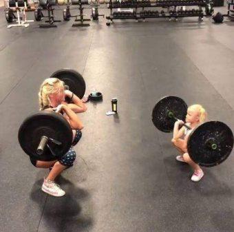 Menina de cinco anos levanta pesos e malha pesado com a mãe